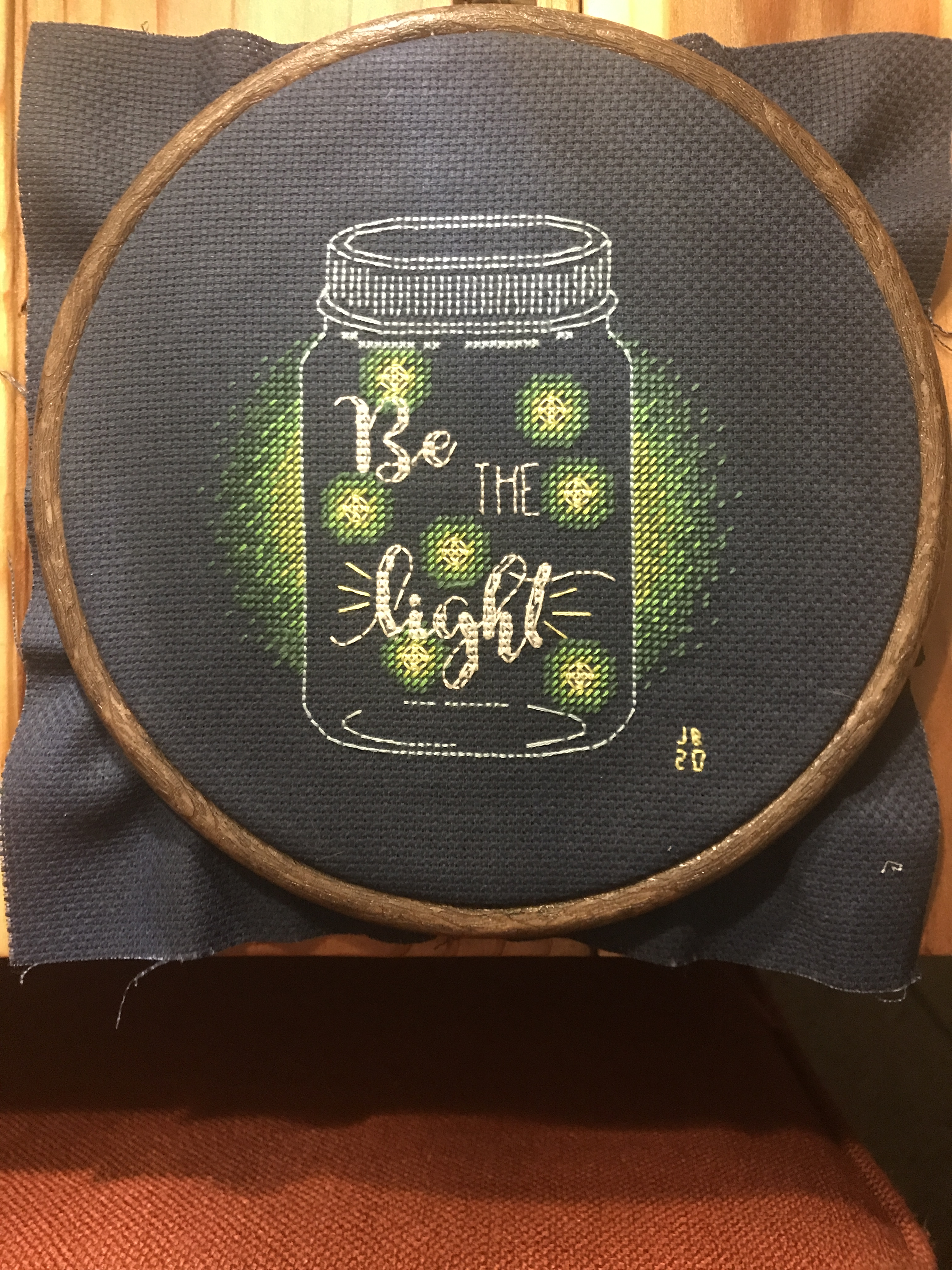 """Cross stitch project featureing a jar with lightning bugs in it and the message, """"Be the light."""""""