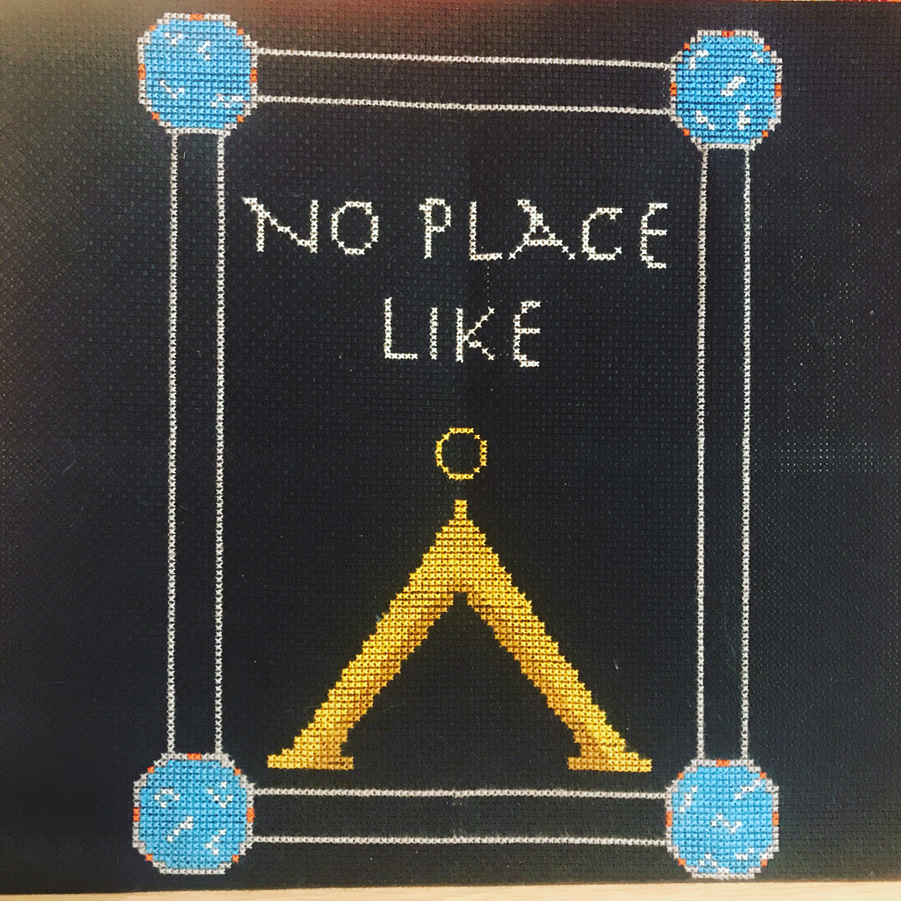 """Cross stitch project reading """"No place like home"""" with the Stargate symbol for Earth in place of the word """"home"""""""