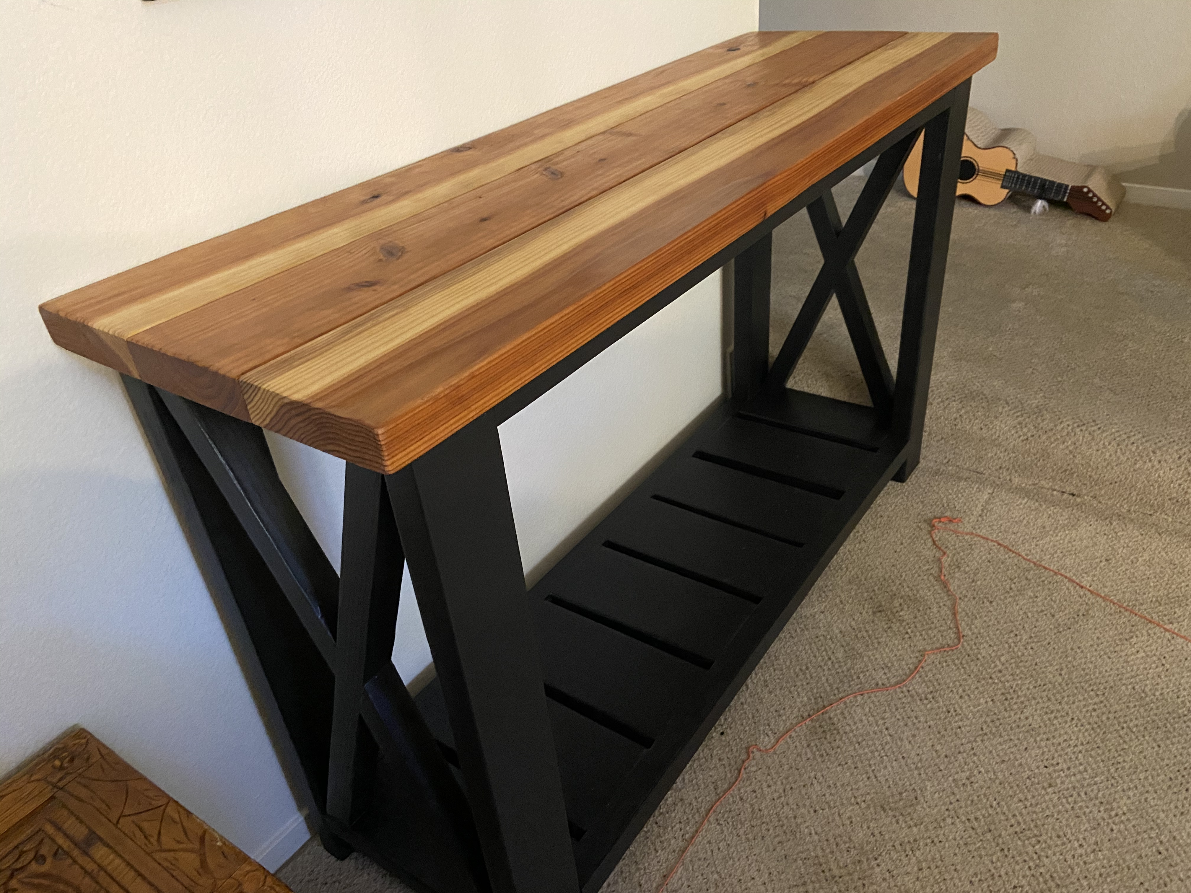 Console table with a black base and a redwood top