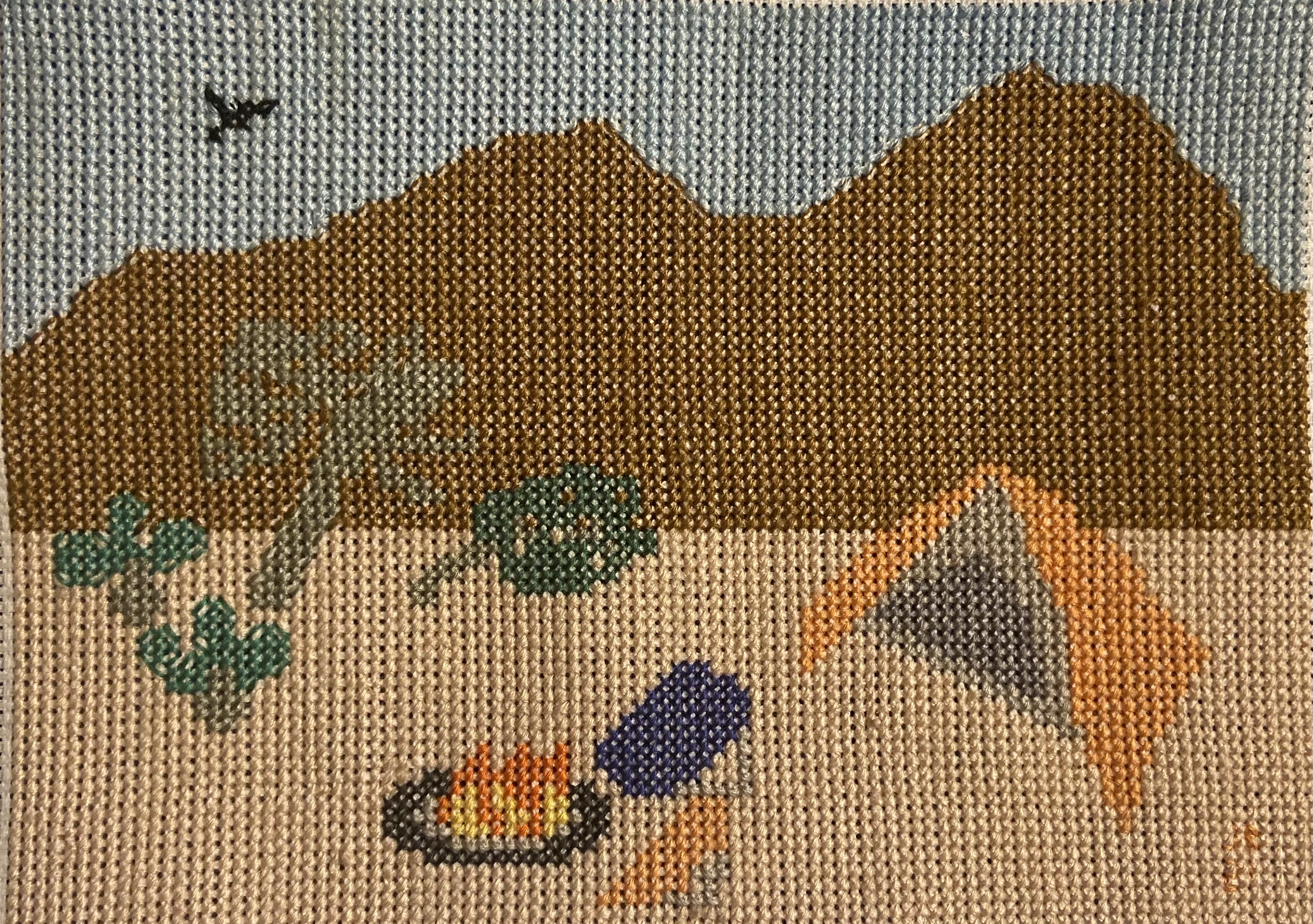 Desert Camping Cross Stitch project with mountains, a black bird, desert plants, a tent, chairs, and a campfire