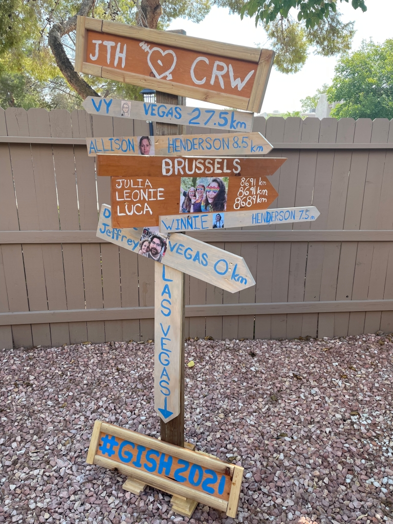 wooden sign with arrows pointing to team members homes