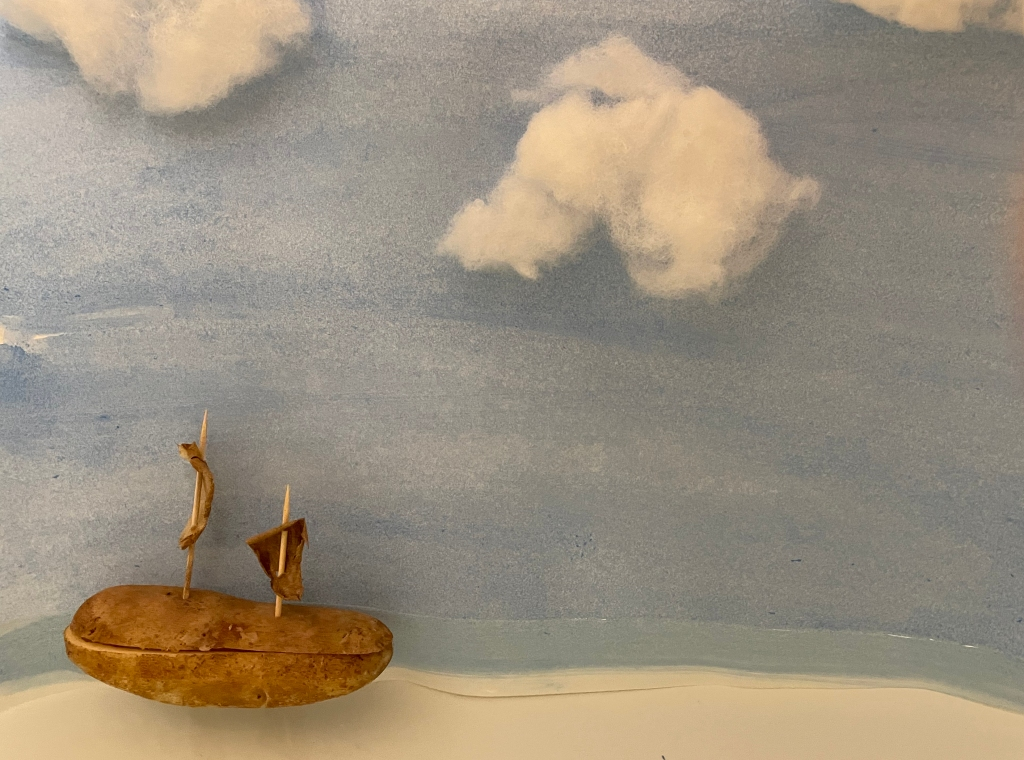 a potato made into a sailing ship and floating in water